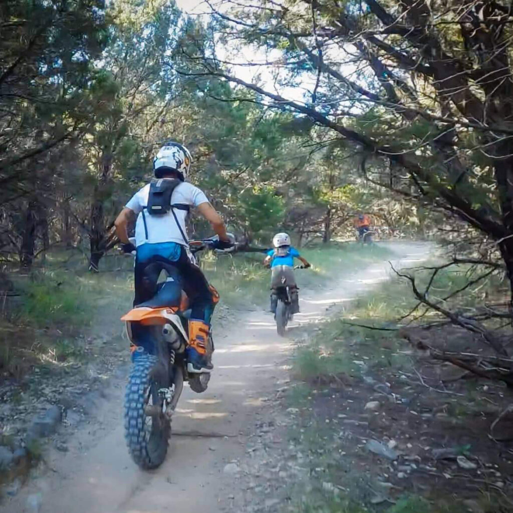 A mother riding dirt bikes with her son.