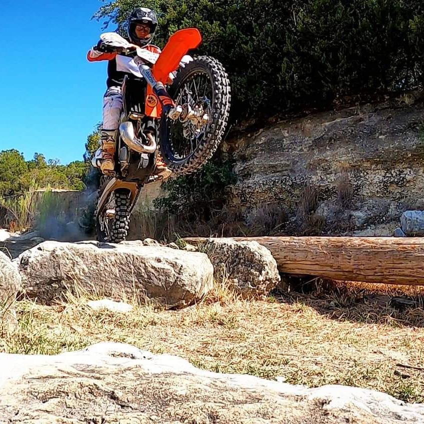 dirt bike wheelie on rocks