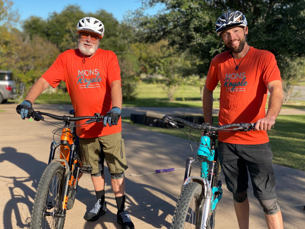 Father and son mountain bikers smiling