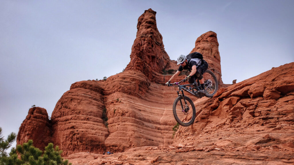 Mountain biker riding their bike down a steep rock