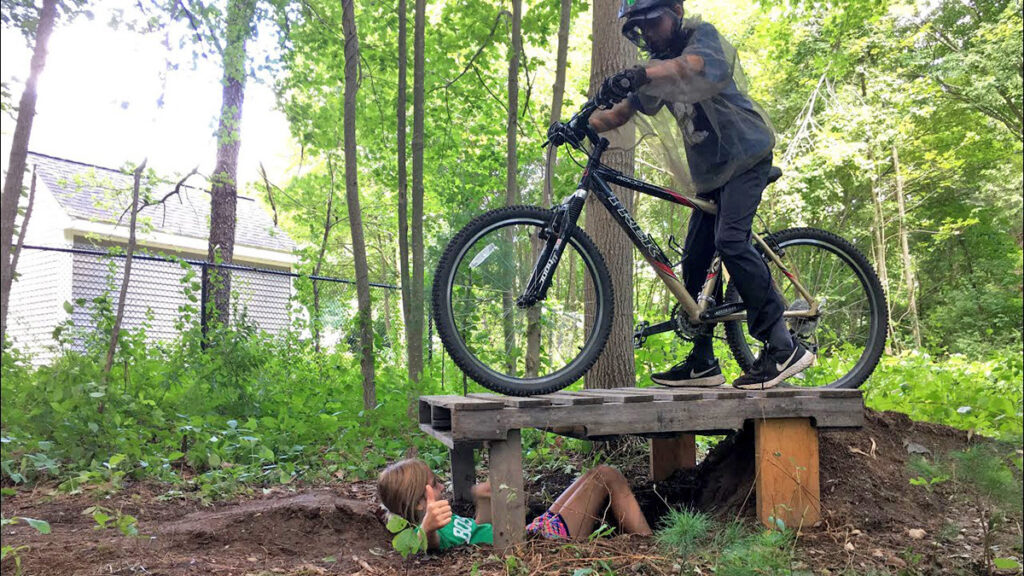 kid riding mountain bike on wooden feature