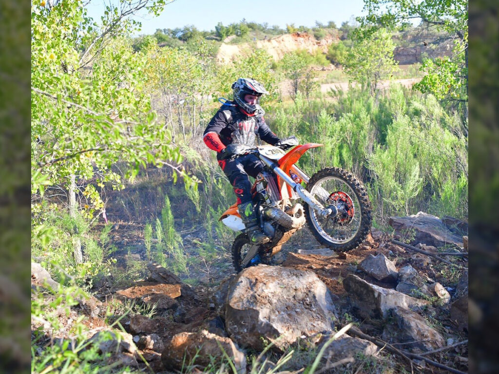 Dirt bike rider riding through a rock garden