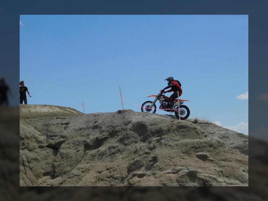 Dirt bike rider cresting a chalky hill climb