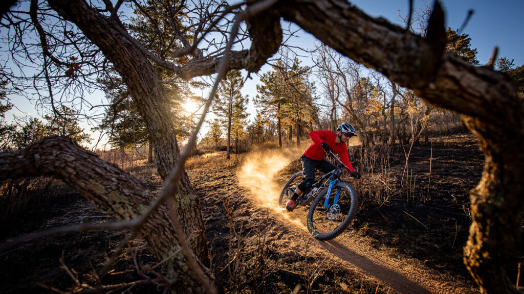 Mountain biker riding a dusty trail with the setting sun beaming behind him.