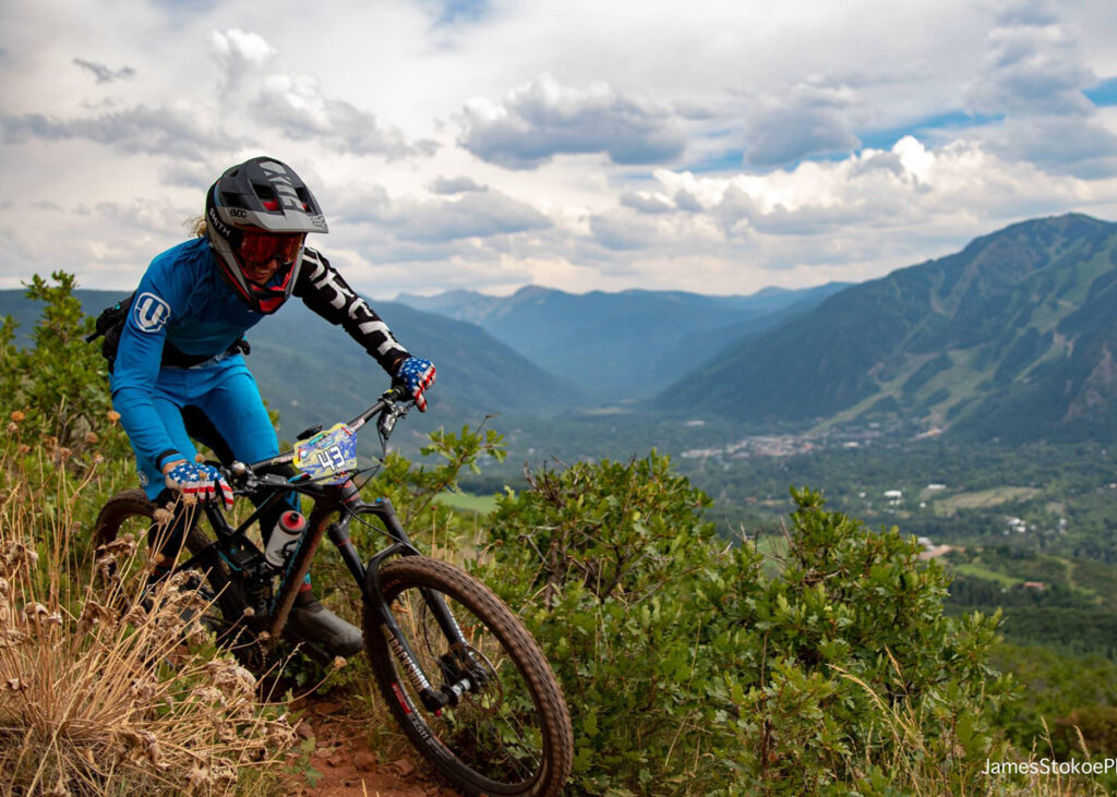 Mountain biker on a trail on the side of a mountain while racing.