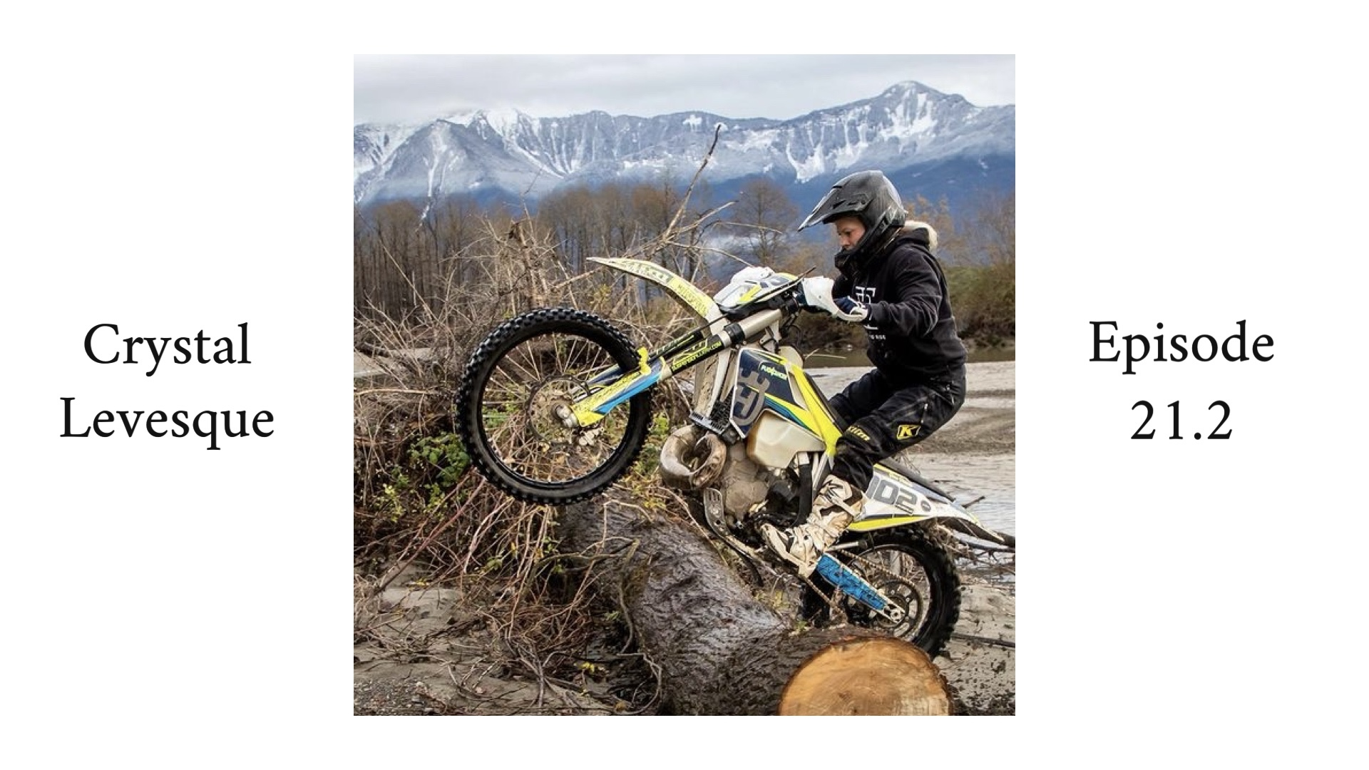 Woman enduro rider riding over a log with mountains in the background.