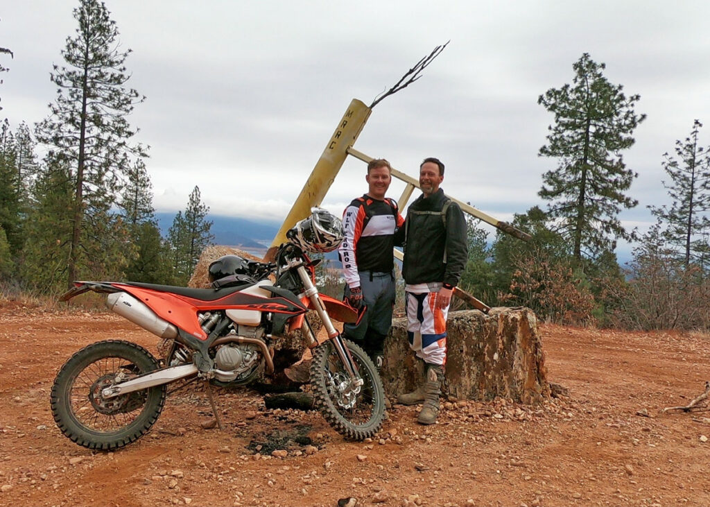 Two dirt bikers standing by the trail.