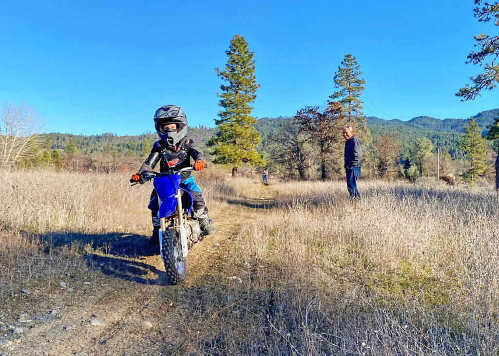 A family riding dirt bikes together.