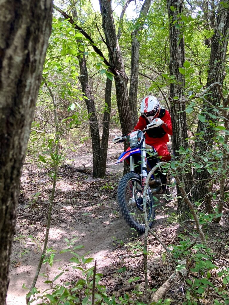 Dirt biker riding through tight singletrack.