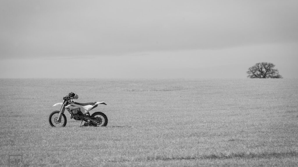 A lonely motorcycle sitting in a field.