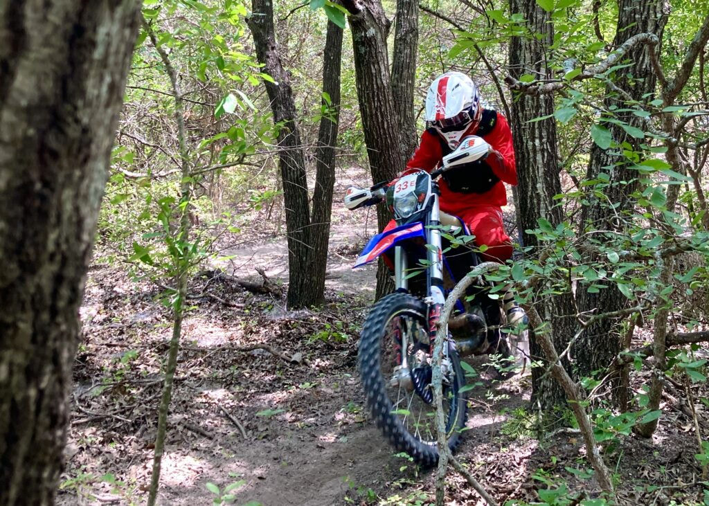 Dirt Bike rider riding between tight trees on a piece of singletrack.